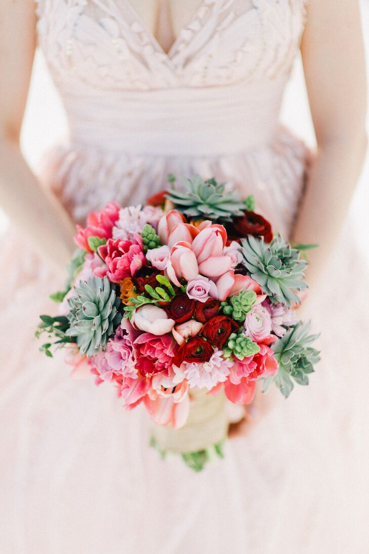 The florals were completely dependent on whatever was local and available. Luckily, Danielle's bouquet turned out completely gorgeous and fitting for the beachy theme: It had succulents blended with bright red ranunculus, blush tulips, roses and peonies.