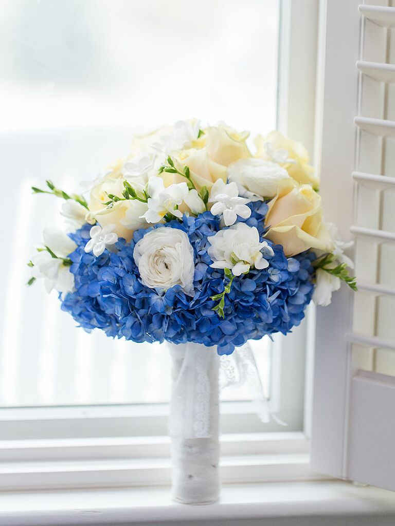 Blue and white wedding bouquet with hydrangea, ranunculus, freesia, roses, stephanotis