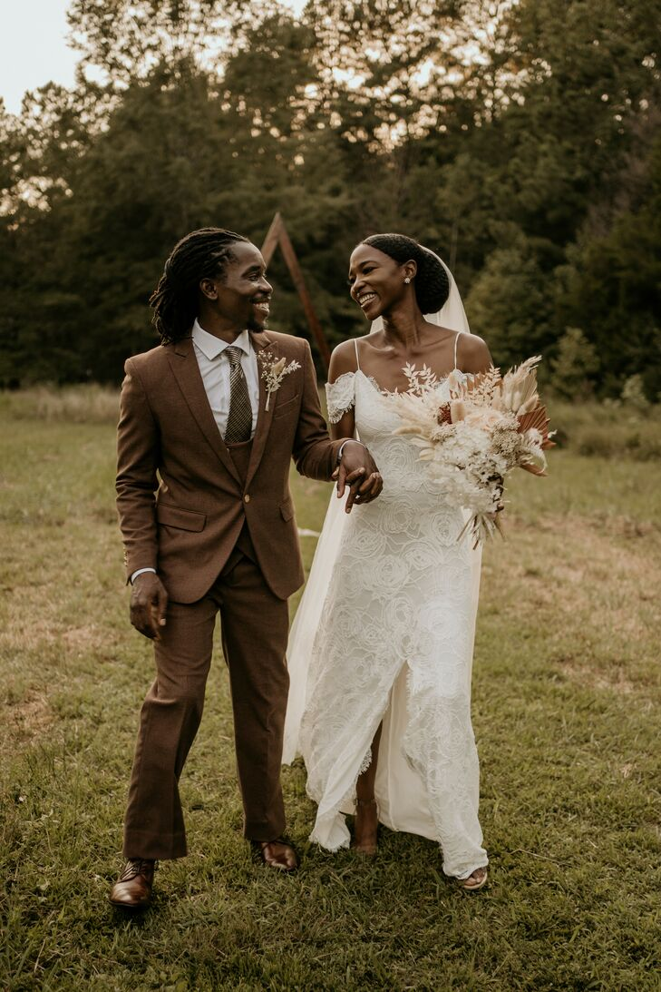 Bride and Groom Holding Hands and Smiling in Field