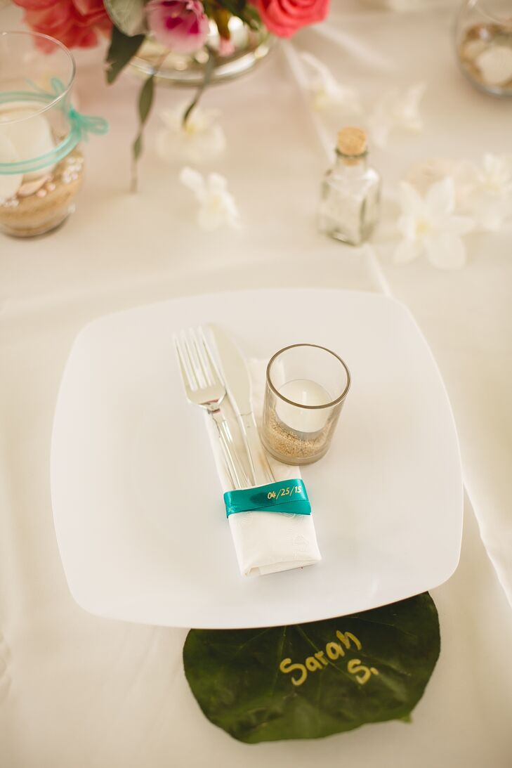 A teal piece of ribbon was marked with the wedding date wrapped around silverware, then arranged on top of white square plates at each place setting.