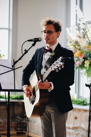 Groom Playing Guitar During Ceremony