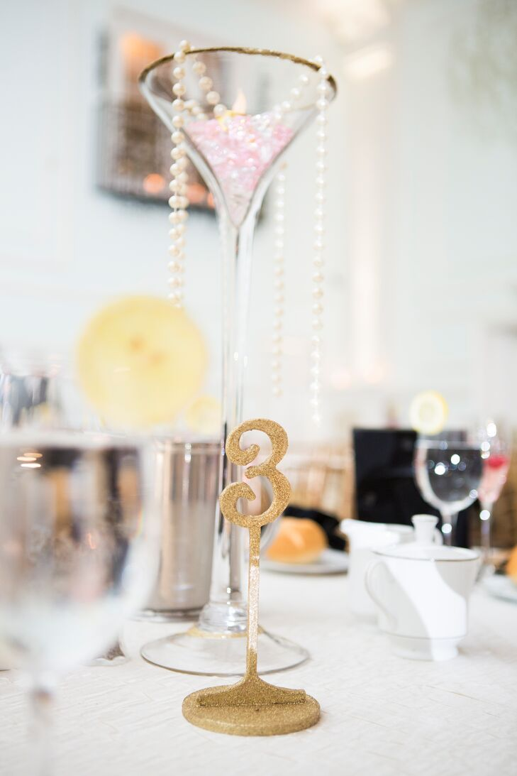 Since Mari loves gold and glitter, it wasn't a surprise that their standout table numbers featured both accents at Cescaphe Ballroom in Philadelphia, Pennsylvania. The couple marked each table with a three-inch gold shimmer number. Its stand coordinated with the tall martini glass-inspired centerpieces and its gold glitter rim.