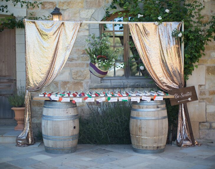 A table of escort cards was displayed atop two large, wooden barrels under a canopy of metallic, draped fabric.