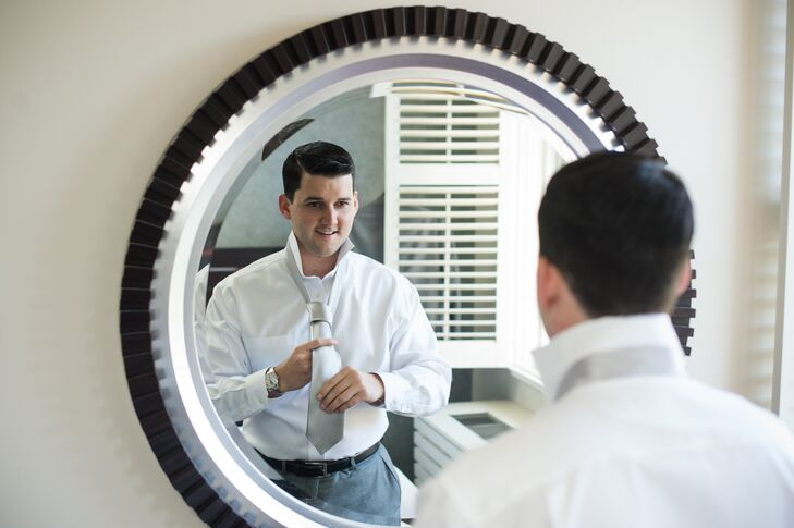 Groom Getting Ready in Mirror with Silver Tie