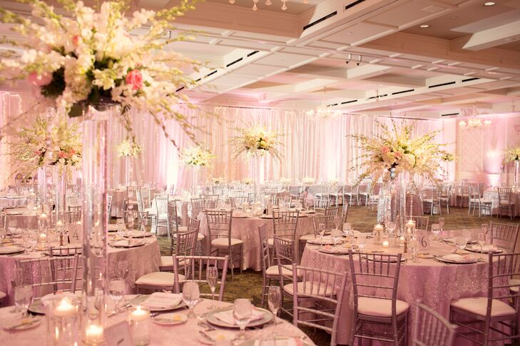 The all-pink wedding decor included pale pink curtains and glittery pink table linens and place settings. Tall, ethereal centerpieces featured an assortment of pink and ivory roses and orchids for contrasting textures.