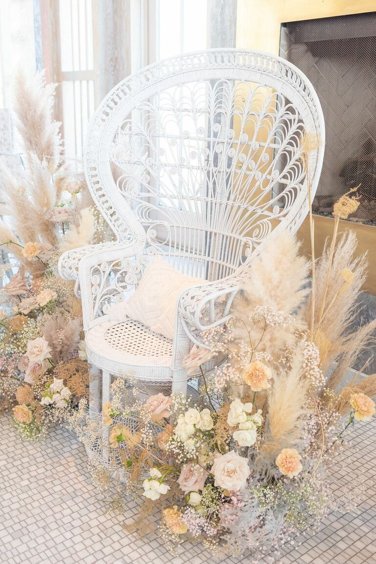 White peacock chair surrounded by pampas grass and peach roses