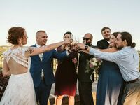 Bride and groom champagne toast with maid of honor and wedding party