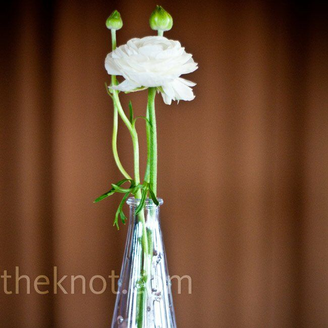 Along with the bouquets as centerpieces, Joy bought little bud vases to hold white ranunculus and baby's breath.