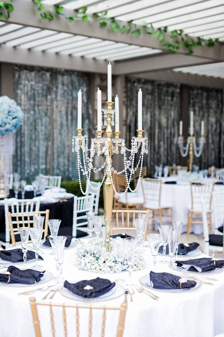 Reflecting the evening's opulent vibe, alternating reception tables were topped with gilded candelabras draped with beaded swags. Halos of lush white florals stood at the base and white taper candles flickered softly in the moonlight.