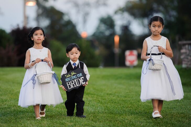 "The flower girls wore white dresses and carried white baskets filled with rose petals while John's nephew carried a chalkboard sign that said ""Here Comes Your Bride."""