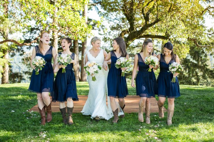 Allyson chose elegant A-line dresses for her bridesmaids in a classic navy color that allow them to wear the dresses again with ease. For a touch of country charm, the girls paired the look with brown cowboy boots.
