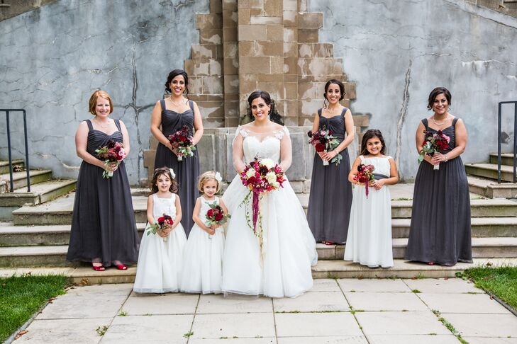Roxanne's bridesmaids wore floor length Amsale dresses in gray, and they carried smaller versions of the bridal bouquet.