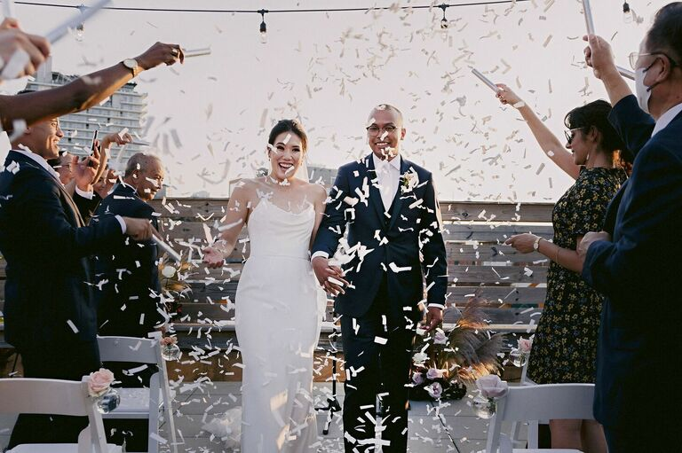 Couple exiting wedding ceremony with cascade of white confetti