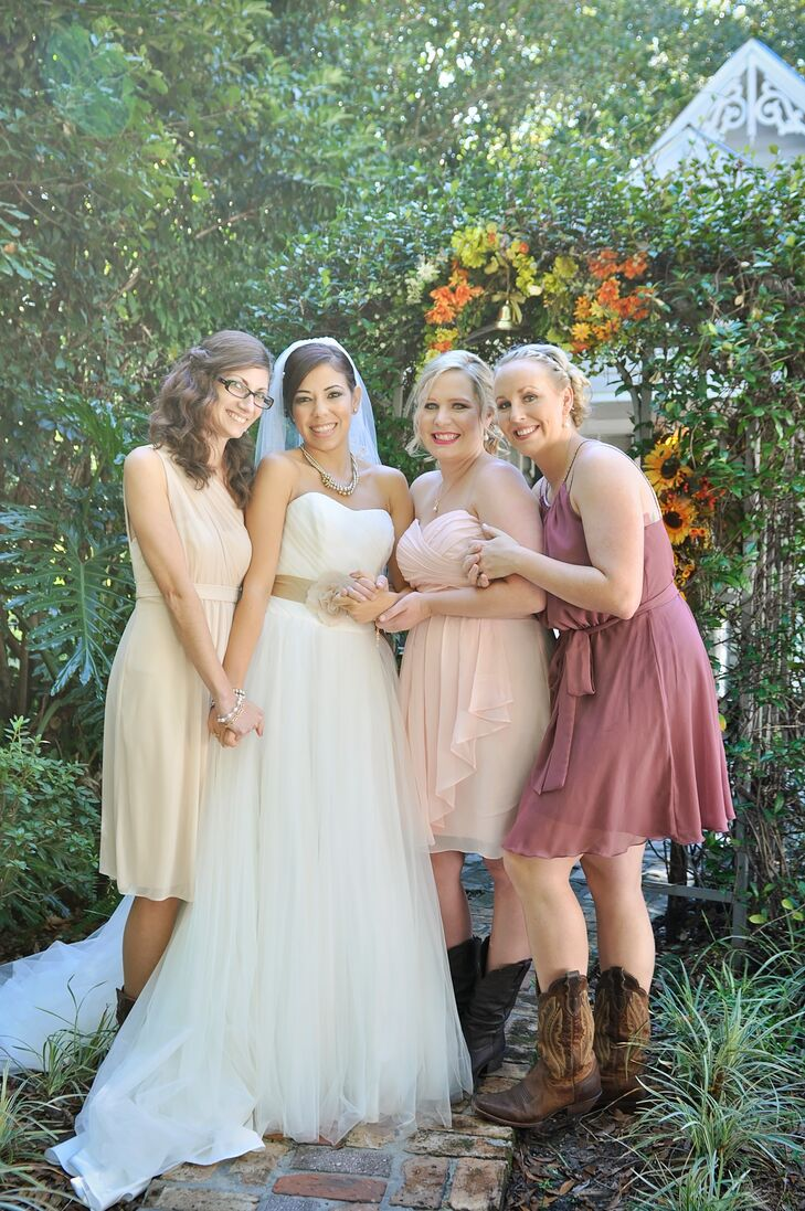"""Rather than just picking one look for the bridesmaids, they went with three. Each woman chose her knee-length chiffon dress in a dusty rose, ivory or blush hue. While their makeup, hairstyles and dress styles differed, the looks were tied together with these dark cowboy boots. """"I wanted them to feel comfortable,"""" Heather says."""