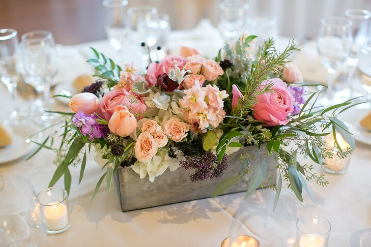 Twisted Willow Florist created centerpieces that featured flower boxes filled with blush, pink and purple blooms and votive candles.