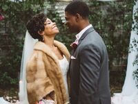 Bride wearing faux fur coverup at winter wedding with groom