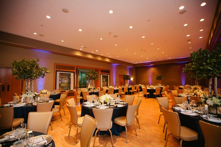 The tables were decorated with a combination of high and low centerpieces, navy shimmer pin tuck linens and white napkins. The couple chose blue uplighting to add ambience.