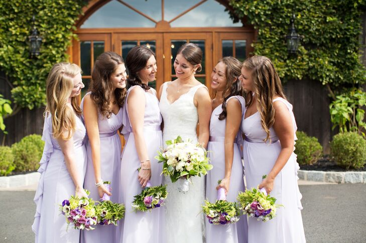 Bridesmaids wore floor-length flowing lilac gowns and carried bouquets with pops of purple blooms.