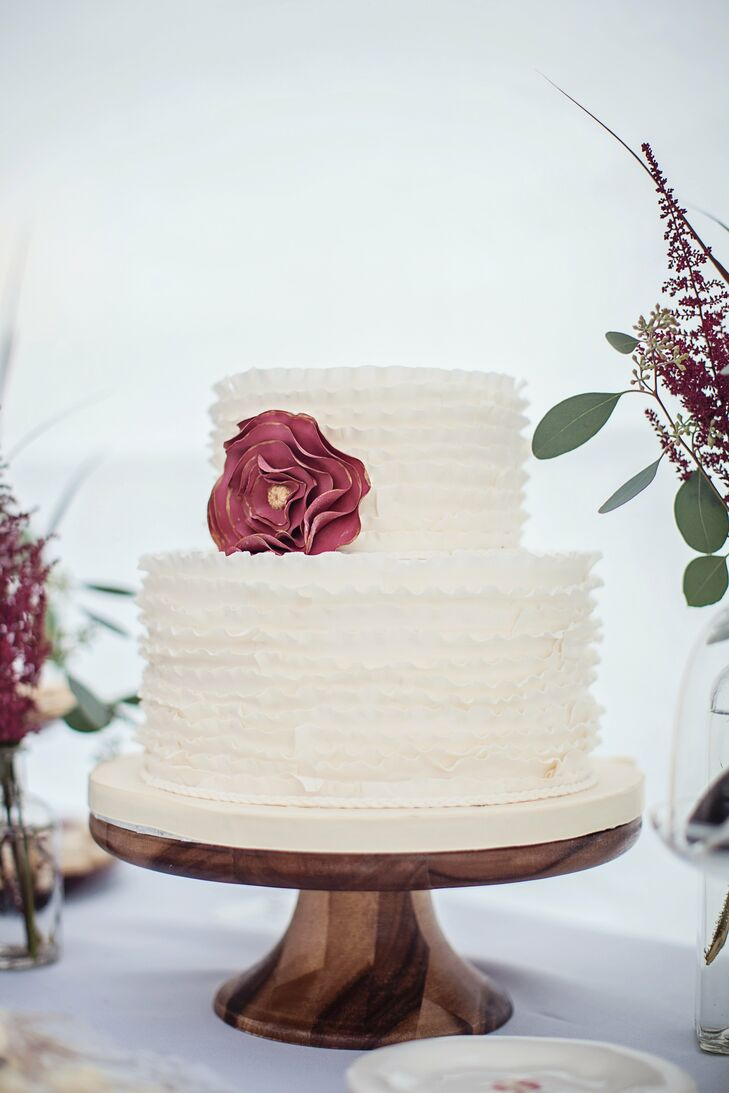 The couple chose a two tiered lemon cream cheese buttercream cake, decorated with ruffles and an off centered red sugar rose.