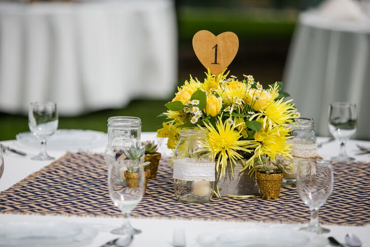 Dining tables were covered with navy blue and tan runners in a Greek key pattern. Canary yellow flower centerpieces were filled with roses and chrysanthemums and a heart-shaped table number stuck up in the middle. The centerpiece was surrounded by mason jars wrapped in lace and burlap.