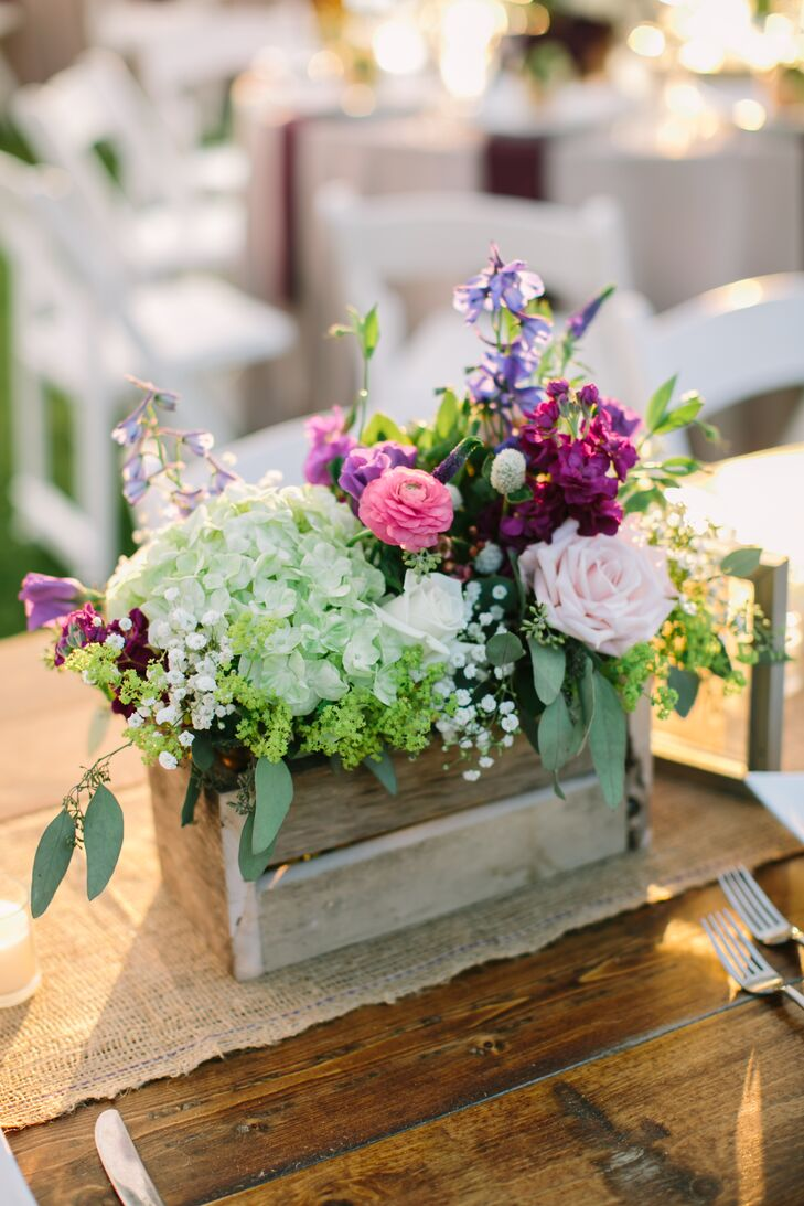 Set against a backdrop of brilliant green landscape, natural linens and rustic wood, the centerpieces truly popped. Bundles of hydrangeas, roses, ranunculus, stock and an assortment of wildflowers in shades of pink, purple, white and peach brought the decor to life with their bright, summery colors and just-picked freshness.