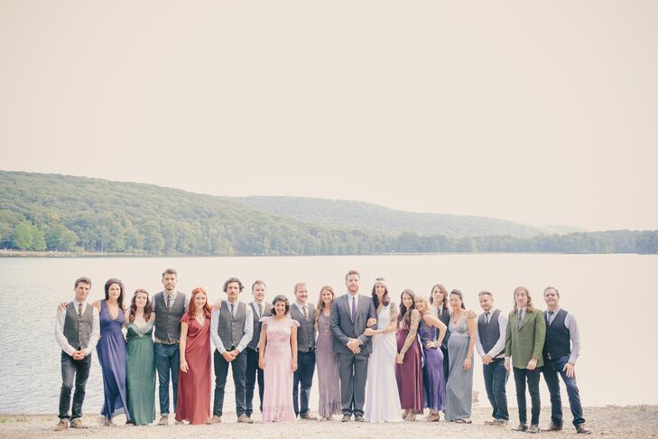 Andrea and Chuck stood with their large wedding party outside near the waterfront at the camping grounds in Sloatsburg, New York, where their wedding took place. The bridesmaids wore vintage slip dresses that were dyed the color of their choice, while the groomsmen wore casual gray vests with colorful striped ties.