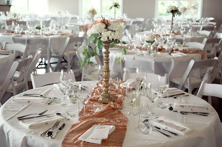 Sparkly blush gold table runners added shimmer to each white dining table, topped with a floral centerpiece of a high or low arrangement of white and pink flowers.