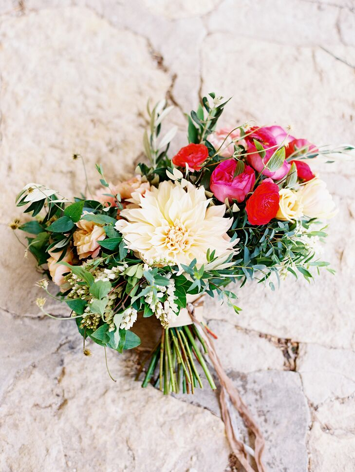 Kristina asked her florist to create a cascading bouquet for her to carry down the aisle that would fit with the wedding's organic, natural vibe. The stunning bouquet was filled with wispy greenery, red ranunculuses, ivory dahlias, bright pink peonies and cream-colored roses, giving off a soft, romantic look.