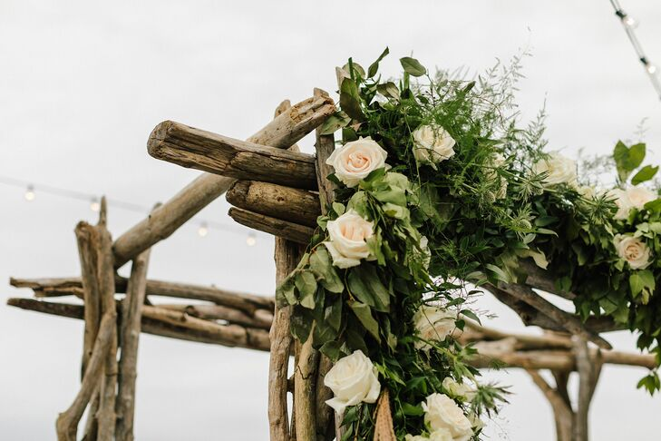 Roses and Greenery on Rustic Wood Wedding Arch