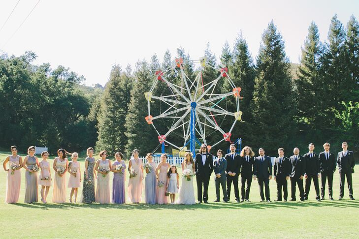 Marisa and Kyle stood in a line with their wedding party outside at Calamigos Ranch in Malibu, California, with the Ferris wheel on the property right behind them. The bridesmaids wore a variety of dresses in different styles, colors and lengths, while the groomsmen matched Kyle and wore black Tom Ford tuxedos paired with bow ties.
