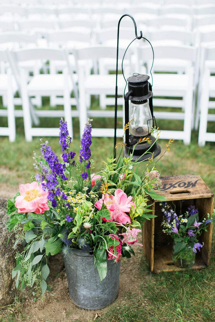 Guests were immersed in the evening's rustic theme from the moment they arrived to the ceremony, greeted by a display of antique lanterns, vintage soda crates and cascading arrangements of bright pink and purple flowers in metal milk pails.