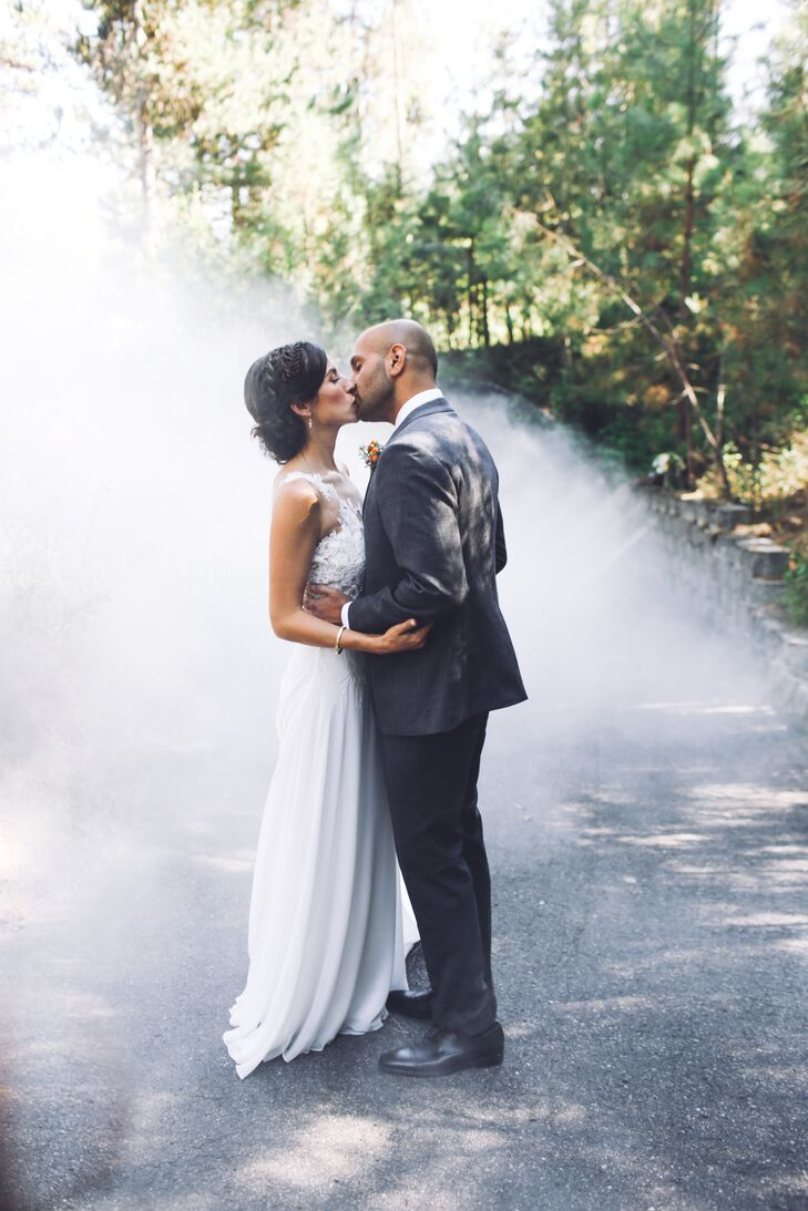"Anish's dark gray suit was made by Indochino, and Amanda's Atelier Provonias gown had a floral overlay. ""It was so comfortable and a perfect fit for my style and the lakeside wedding location,"" Amanda says. ""The lacy chest overlay and straps were subtly reminiscent of leaves and flowers."""