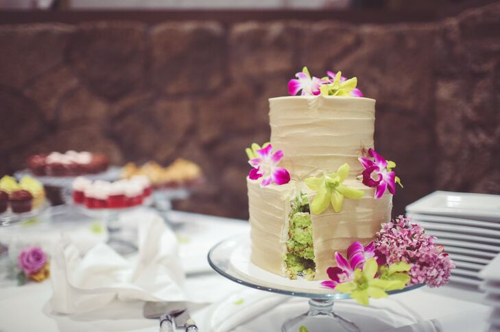 The two-tier wedding cake was minimally decorate with ivory buttercream icing and bright purple and green orchids to complement the tropical setting. Both the main wedding cake and the groom's cake were Dana and Steven's favorite flavor--pistachio! The couple also served an assortment of cupcakes in lemon chiffon, chocolate raspberry, chocolate peanut butter, red velvet, and carrot cake.