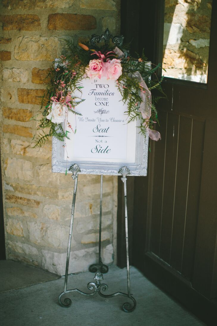 """Guests were greeted to to the ceremony by this black-and-white sign that said, """"As two families become one, we invite you to choose a seat, not a side."""" Not afraid to bring the outside in, the sign was decorated with a lush pine garland and two pink roses in the center to match the color palette."""