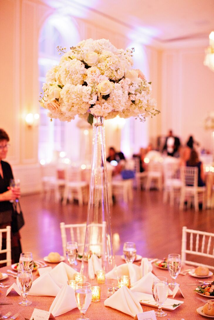 The centerpieces were tall inverted trumpet glass vases with a round bouquet of white roses