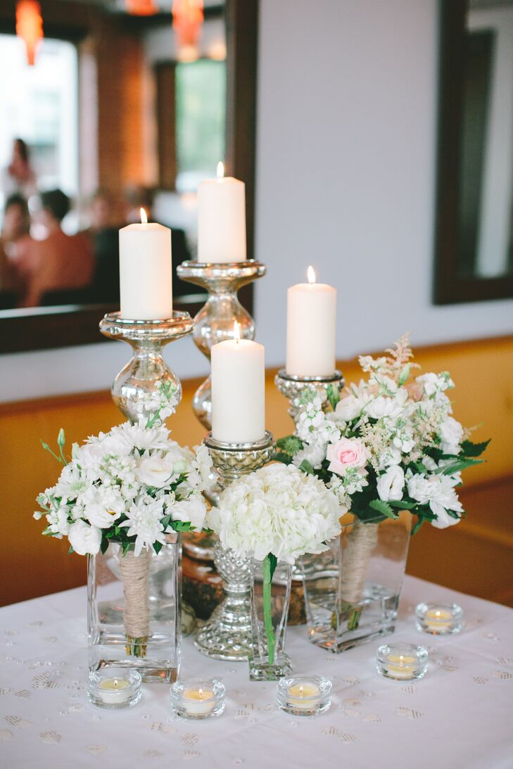 Meghan and her bridesmaids reused their bouquets to decorate the reception tables. They dropped the gorgeous, textured arrangements into modern, square glass vases to match the simple hydrangeas. Tiered white pillar candles added plenty of romance to the space.