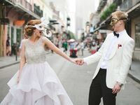 Newlyweds holding hands during second line celebration with mardi gras masks