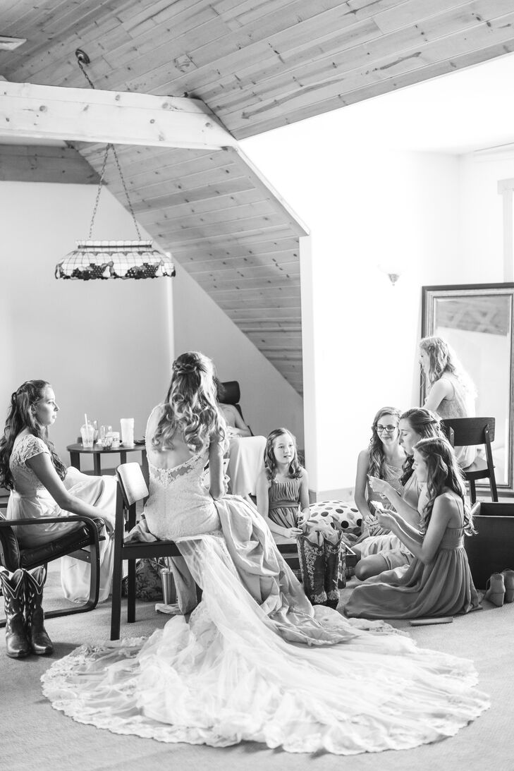"""Abigail and her bridesmaids prepped at her parents' house (the site of the wedding) in Bend, Oregon. """"My gown was a Martina Liana design. The straps were delicate, intricately beaded lace that opened to a low back. It was elegant, but the amount of lace and detailed beadwork covering the dress made a rather western, eclectic wedding theme feasible to work around."""""""
