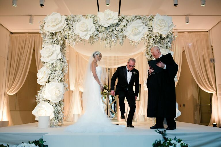 Groom breaking glass during Jewish wedding ceremony under rose-covered chuppah