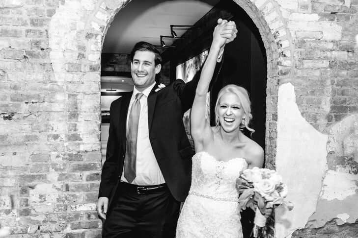 Corinne and John entered the reception space at Mount Washington Mill Dye House in Baltimore, Maryland, with their hands up in celebration. Corinne wore a gorgeous Allure Bridals ivory dress with a sweetheart neckline and a bodice accented in lace applique and English net.