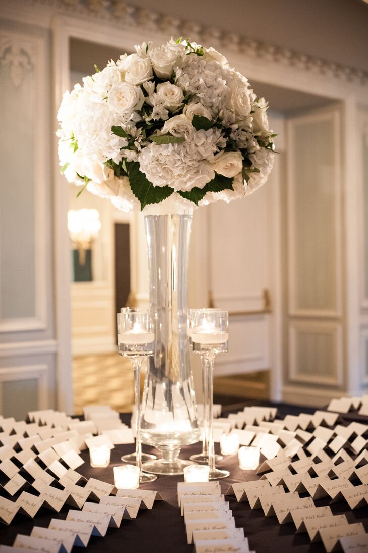 Escort cards at the reception were displayed on a round table. At the center of the table were votive candles, floating candles and a tall arrangement of white hydrangeas and white roses.