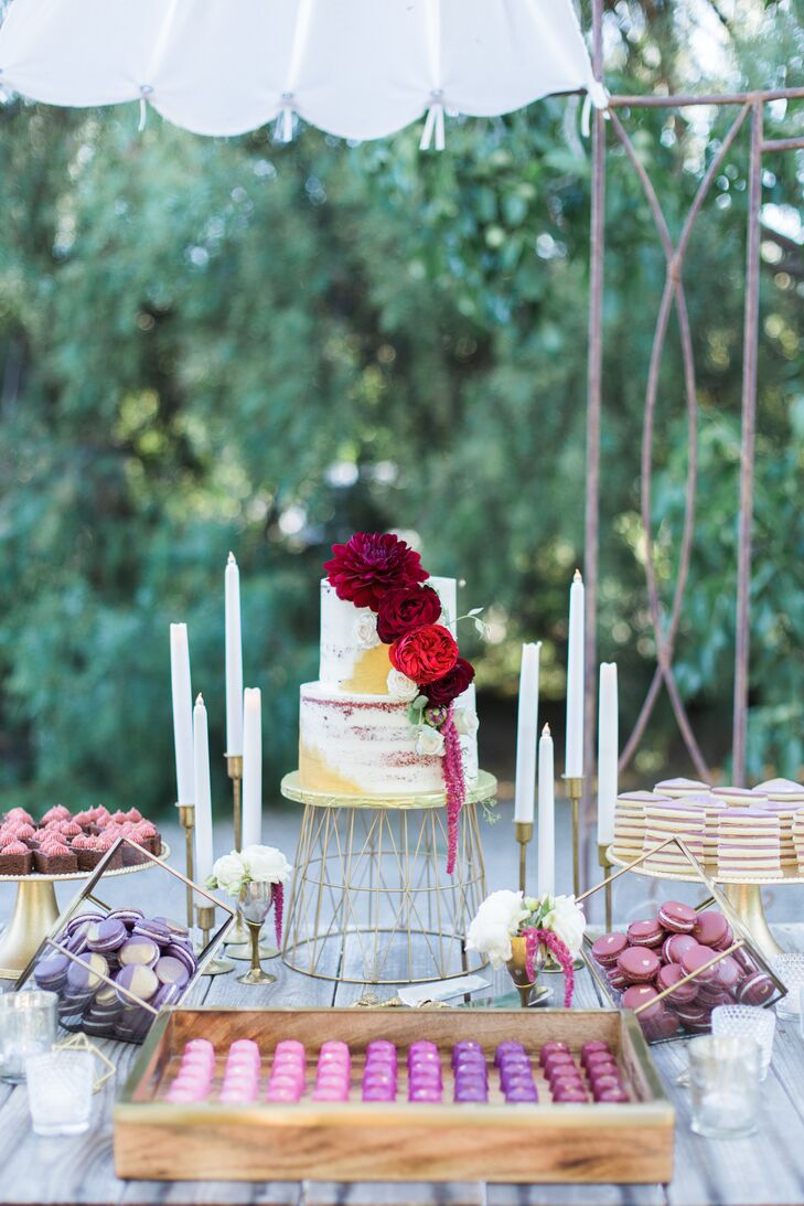 Paso Robles' Paper Cake Events created the couple's simple two-tier rough-frosted wedding cake and topped it with crimson blossoms. The cake was accompanied by a tableful of other desserts.