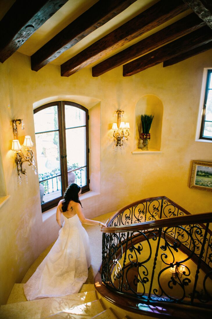 As Alyssa walked down the elegant staircase, her wedding dress train trailed elegantly behind her. She wore a strapless white Anna Meia Couture gown with a Chantilly lace overlay.