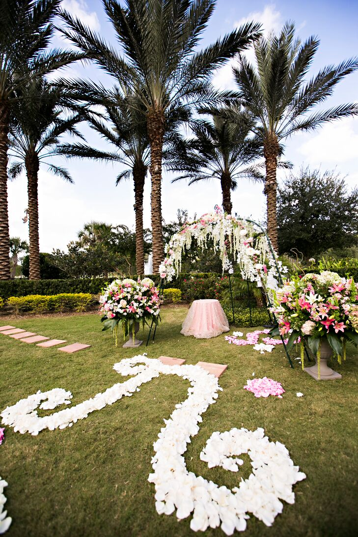 """With the help of Island Girl Flowers, Kelley and Kegan turned their palm-tree-lined ceremony space into a """"garden."""" White flower petals lined the aisle in the shape of their initial and a scroll design for a whimsical touch along the aisle. Two overflowing arrangements of stargazer lilies, hydrangeas and roses accented the wedding arch, which resembled something out of a dream. Lilies of the valley were intertwined with roses for a romantic touch against the wire frame."""