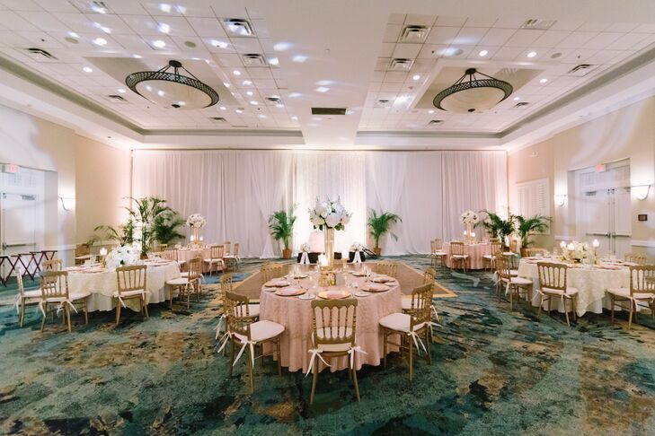 The couple decorated each round reception table with  ivory or blush linens, gold chairs, gold chargers, gold candlesticks and white hydrangeas and rose centerpieces for a romantic look.
