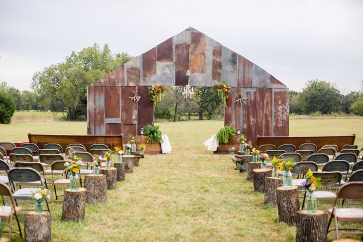 Tin Barn-Shaped Wedding Backdrop with Tree Stumps and Wildflowers Lining Aisle