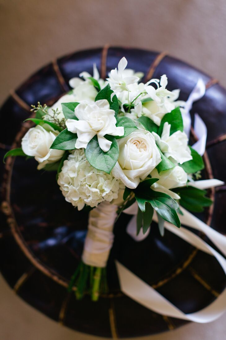 """Grace held an ivory bouquet of gardenia, roses and hydrangeas for the wedding day. """"One small, improvised detail was the letter that Grace wrapped around her bridal bouquet,"""" says the couple., """"One of Grace's bridesmaids (a best friend since childhood) couldn't make it to the wedding at the last minute, but sent a beautiful letter."""""""