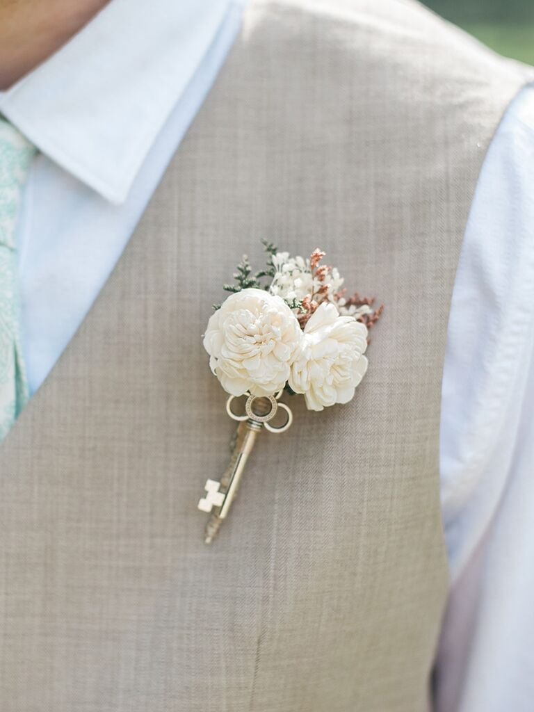 Simple rustic boutonniere with flowers and an antique key