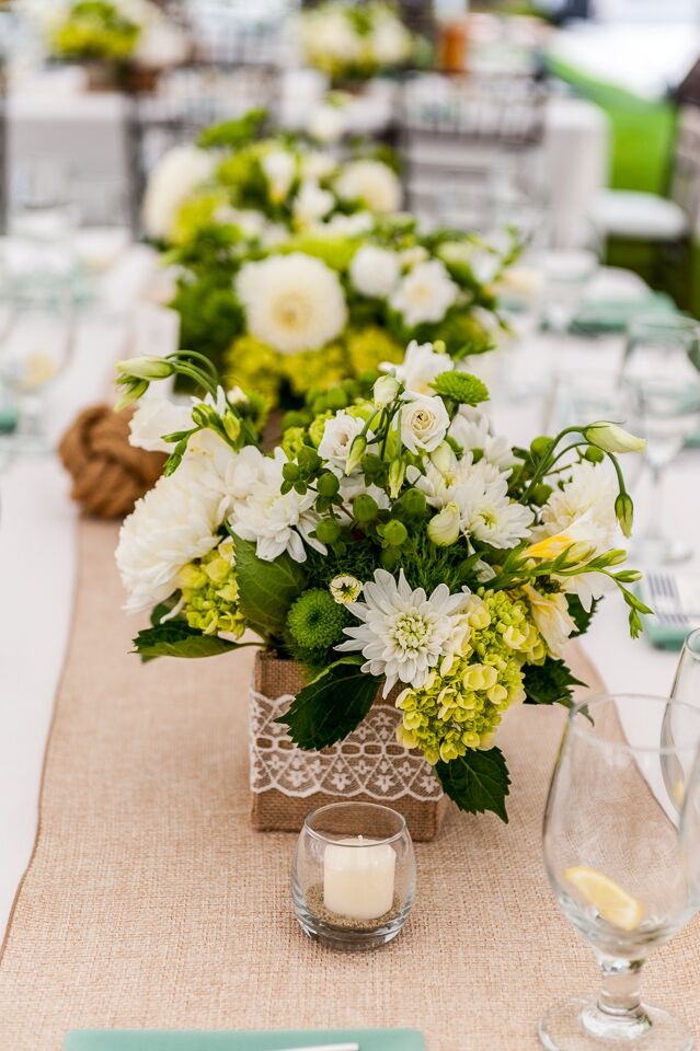 The bride wanted to create eclectic centerpieces based on colors she liked. Although the bride and groom had a nautical theme, they incorporated green, white and yellow into their floral arrangements to keep the color palette feeling classic and fresh.
