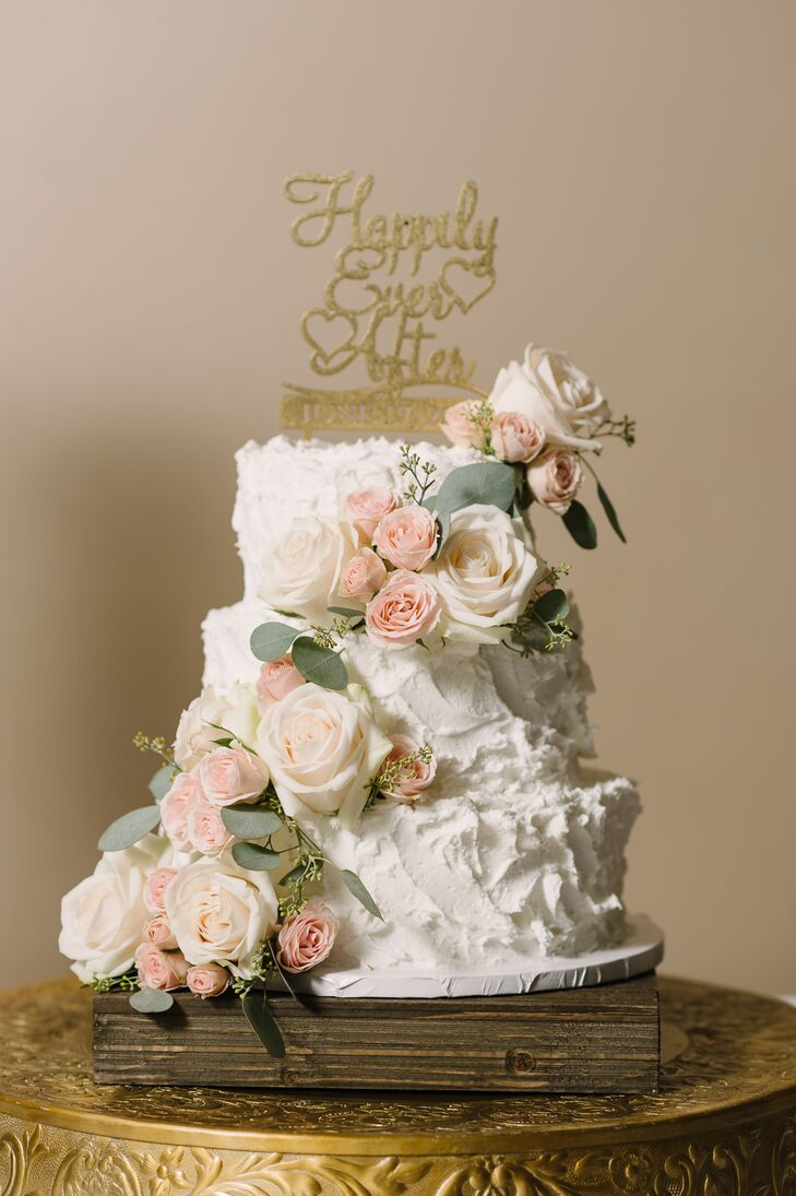 The three-tier white cake featured a cloud frosting design and was adorned with fresh roses and greenery.